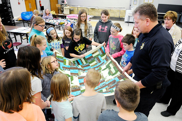 Don Knight | The Herald Bulletin<br /> The quilting club at Summitville Elementary gives a quilt to Town Marshall Shawn McGuire on Wednesday. The club wanted to give practice quilts they created to the Summitville Police Department to keep in their patrol cars in case someone needs them