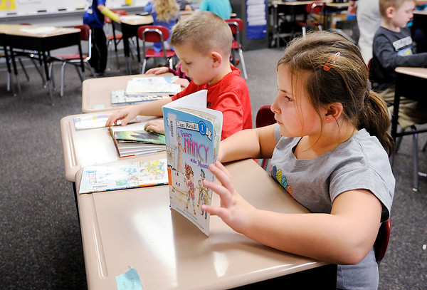 """Don Knight   The Herald Bulletin<br /> Pyper Howard reads """"Fancy Nancy at the Museum"""" in Becky Cords first grade class at Summitville Elementary on Wednesday. Madison-Grant Superintendent Dr. Scott Deetz proposed on Monday that Summitville Elementary School become an early childhood learning center for students in grades kindergarten through two while Park Elementary in Fairmount serve students in grades three through six."""