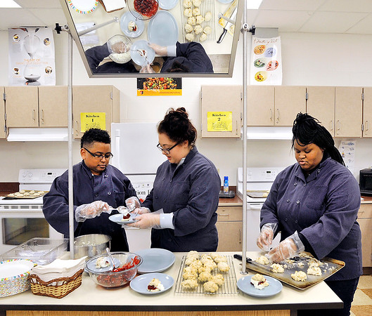 John P. Cleary    The Herald Bulletin<br /> AHS Culinary Arts and Hospitality students Darius Brown, Kiley Dodson, and Yasmina Bennett work together to put together strawberry shortcakes Friday during class.