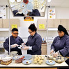 John P. Cleary |  The Herald Bulletin<br /> AHS Culinary Arts and Hospitality students Darius Brown, Kiley Dodson, and Yasmina Bennett work together to put together strawberry shortcakes Friday during class.