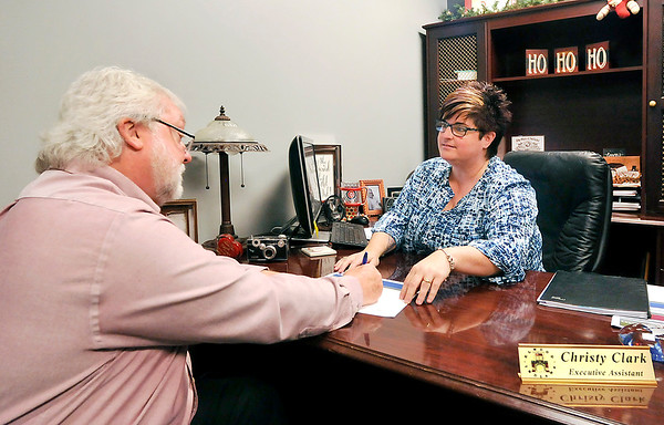 John P. Cleary |  The Herald Bulletin<br /> Christy Clark, administrative assistant to Elwood Mayor Todd Jones, works with Bill Savage, planning director for the city, on upcoming items for her calendar.