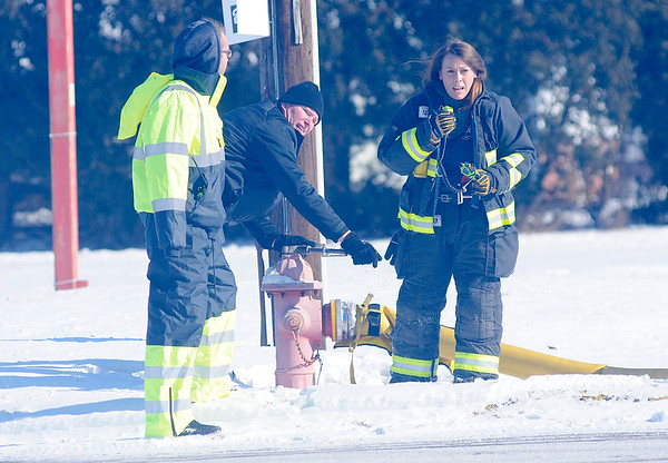 Don Knight |  The Herald Bulletin<br /> Chesterfield Police Chief Billy Ingles turns on a hydrant as firefighter Lauren Muehl radios that the water is flowing during a house fire in the 4300 block of Ind. 32 on Tuesday. Standing to the left is Noah Milburn with the fire department who along with Chief Ingles ran down Ind. 32 carrying the 5 inch hose after the first hydrant they tried didn't work.