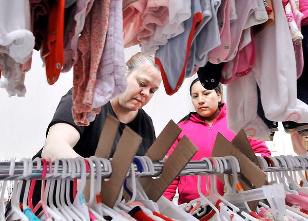 John P. Cleary | The Herald Bulletin<br /> SuzieDee Pardue helps Louisa Santiago pick out clothes from the racks during a recent visit to The Baby Corner at Christ Lutheran Church in Anderson.