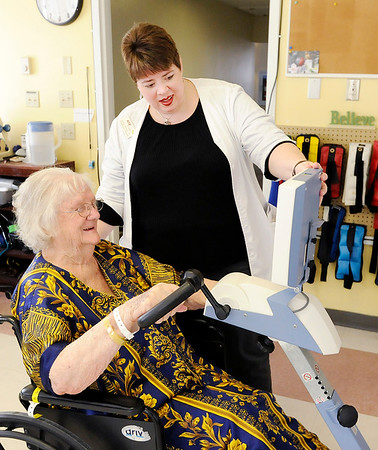 Don Knight |  The Herald Bulletin<br /> Occupational therapist Kathy Moore works with Retha Bell on an exercise bike at Community Northview Care Center on Friday.