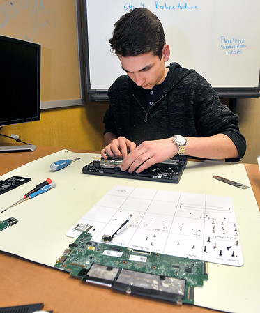 John P. Cleary   The Herald Bulletin<br /> Elwood High School junior James Dobbs works on a student's Cromebook as a member of the school's Tech Team.