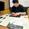 John P. Cleary | The Herald Bulletin<br /> Elwood High School junior James Dobbs works on a student's Cromebook as a member of the school's Tech Team.