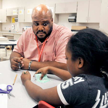 John P. Cleary | The Herald Bulletin<br /> Anderson Elementary third-grade teacher Ryan Miller works with a student on lessons about Dr. Martin Luther King Jr. this past week. Miller will be the keynote speaker for a school-wide assembly honoring King.