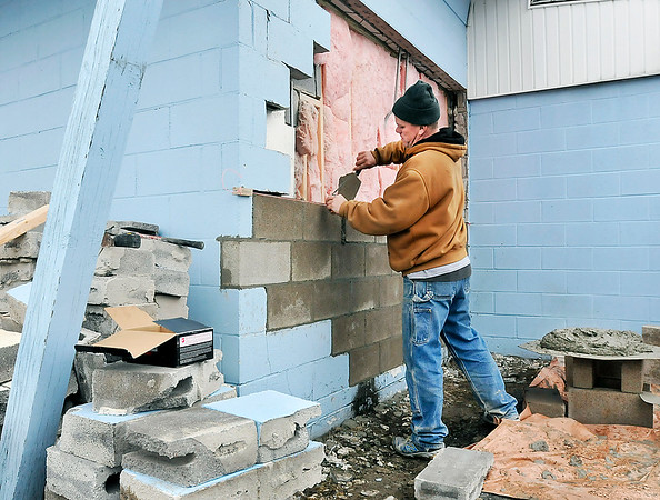 John P. Cleary   The Herald Bulletin<br /> Brent Stiers, of Brent Stiers Masonry, repairs the hole in the back wall of Crack Shot Guns at 715 E. 53rd Street where thieves drove a vehicle into the building Sunday evening and stole an undisclosed numbers of firearms.