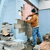 John P. Cleary | The Herald Bulletin<br /> Brent Stiers, of Brent Stiers Masonry, repairs the hole in the back wall of Crack Shot Guns at 715 E. 53rd Street where thieves drove a vehicle into the building Sunday evening and stole an undisclosed numbers of firearms.