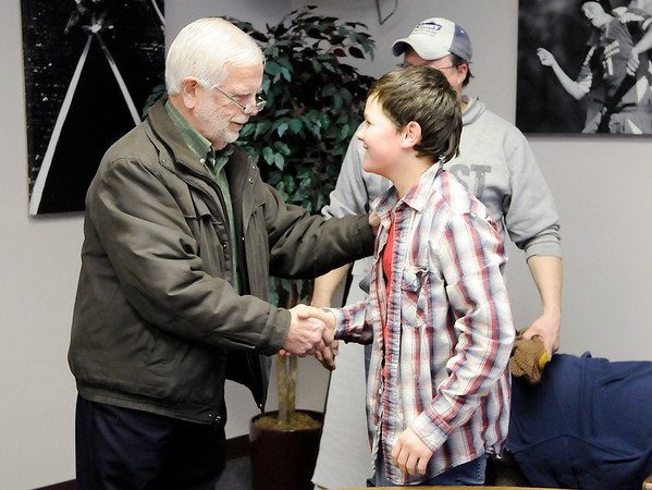 Don Knight |  The Herald Bulletin<br /> Cael Alexander, 12, and his father Jason meet Dennis Swartz at The Herald Bulletin newsroom on Tuesday.
