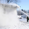 Don Knight |  The Herald Bulletin<br /> Firefighters overhaul a house fire in the 4300 block of Ind. 32 in Chesterfield on Tuesday. The fire started in the garage, officials said, where a space heater was used to keep pets warm.