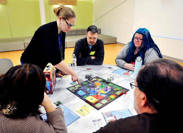 "John P. Cleary |  The Herald Bulletin<br /> Danielle Acton, digital services coordinator for Anderson Public Library, goes over the rules to the board game, ""The Captain is Dead"", during Game Night for Grownups at the library. They have a monthly gaming group at the library for adults only that meets on the second Monday each month."