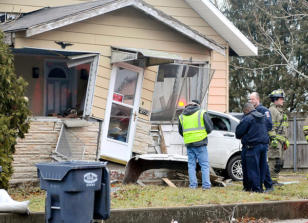 John P. Cleary | The Herald Bulletin<br /> This vehicle lost control Thursday morning while driving west along Eighth Street breaking off a power pole, hitting a fire hydrant before ending up into this house at 2112 West Eighth Street.