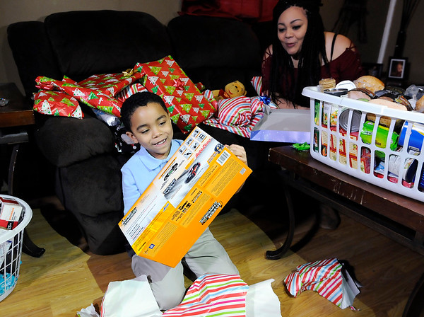 Don Knight |  The Herald Bulletin<br /> Pamela Graves looks on as her son Lamar unwraps a remote control car on Wednesday. Hoosiers with Hearts and the Salvation Army of Henry County decided to help the family after hearing about their presents being stolen on Christmas Eve.