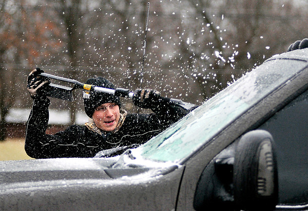 John P. Cleary | The Herald Bulletin<br /> Bobby Hoffman, an Anderson University freshman, clears his windshield of ice Friday morning in the Fair Commons parking lot after overnight freezing rain and sleet fell over the area. A winter weather advisory remains in effect until 10 PM tonight locally.