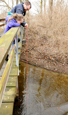 Don Knight |  The Herald Bulletin<br /> Inspired by an online video Randy Bott and his daughter Phoenix, 6, use a magnet to see what they can find on the lake bottom around the Shadyside lake foot bridge on Tuesday.