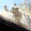 John P. Cleary |  The Herald Bulletin   FILE PHOTO<br /> Anderson firefighters battle a house fire, here venting the roof, at 2219 Central Avenue Thursday afternoon.