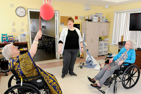 Don Knight |  The Herald Bulletin<br /> Occupational therapist Kathy Moore looks on as Retha Bell, left, and Phyllis Bryant hit a balloon back and forth in an exercise to work on their coordination at Community Northview Care Center on Friday.