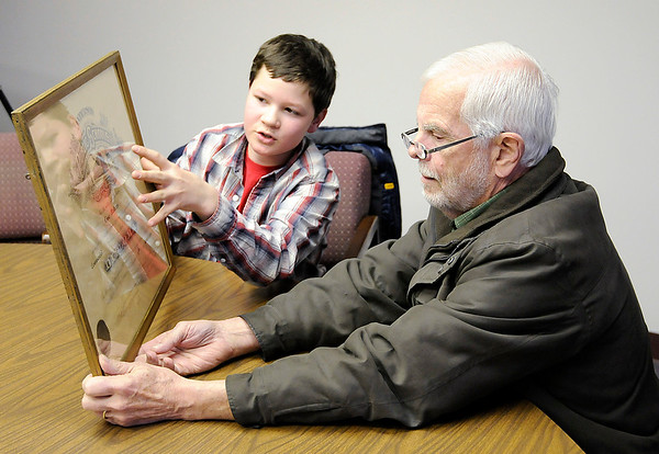 Don Knight |  The Herald Bulletin<br /> Cael Alexander, 12, talks to Dennis Swartz about a diploma for Lena Mather's from 1919 that he found behind a framed picture he bought at a garage sale as the two met at The Herald Bulletin newsroom on Tuesday. Swartz was intrigued by the story of the diploma and researched Mather's and found her son living in Oregon.