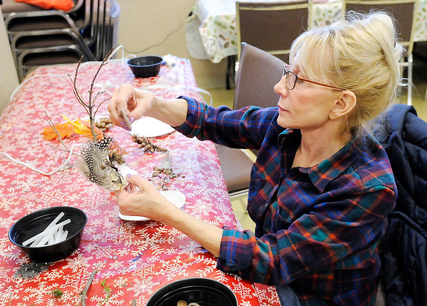 Don Knight | The Herald Bulletin<br /> Linda Ulicne attaches feathers to her mask during a Nature Mask workshop at Mounds State Park on Saturday.