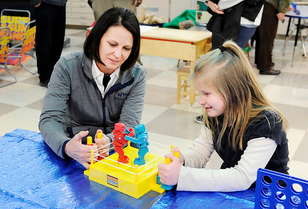 Don Knight   The Herald Bulletin<br /> NTN HR manager Teresa Amburgey plays Rock 'Em Sock 'Em Robots with Zoey Burns during the opening of the new awards room at Anderson Elementary on Wednesday.