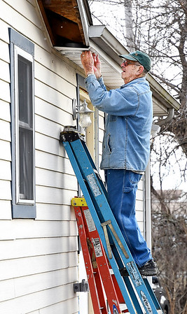 John P. Cleary | The Herald Bulletin<br /> Habitat for Humanity volunteer Don Chastain installs a air vent cover in the soffit on a house they are rehabbing on Morton Street in Anderson.