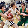 John P. Cleary | The Herald Bulletin<br /> Lapel's Bryce Carpenter drives the baseline against New Castle's #40, Collin Blessinger as Nicholas Grieser, of New Castle comes in from behind to try to steal the ball.