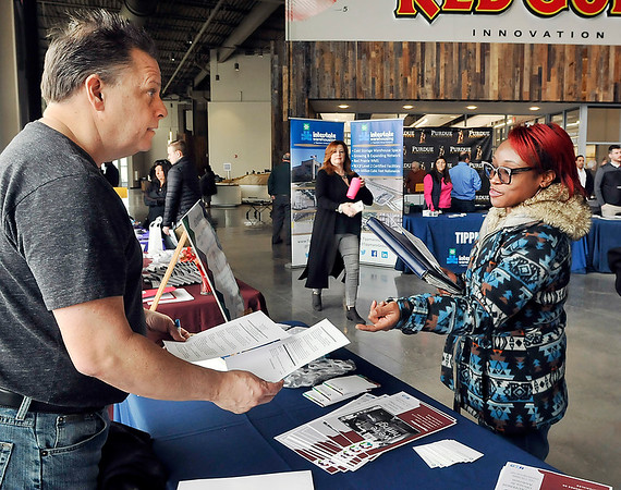 John P. Cleary   The Herald Bulletin<br /> Ted Martin of Morales Group talks with Ashanti Thompson as he looks over her resume during the Hire Anderson Job Fair Friday at Purdue Polytechnic.