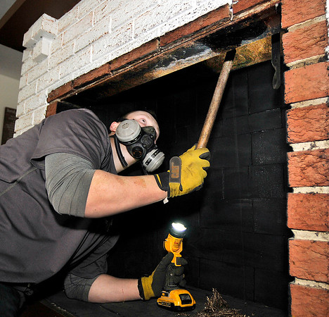 John P. Cleary | The Herald Bulletin<br /> Brian Matheney, of Soot & Cinders Chimney Sweeping, cleans out the flue of this chimney as they prepare to install a fireplace insert in this rural Madison County home Monday.