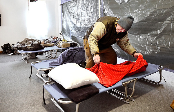 John P. Cleary | The Herald Bulletin<br /> Dave Pettigrew folds his blanket after spending Tuesday night at the Main Street Church of God warming center. Pettigrew lives in rural Madison County but decided that staying at the farm by himself in this extreme cold would be a bad risk.