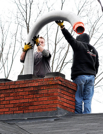 John P. Cleary | The Herald Bulletin<br /> Brian Matheney and Chris Matheney, of Soot & Cinders Chimney Sweeping, install a new flue liner as they prepare to install a fireplace insert in this rural Madison County home Monday.