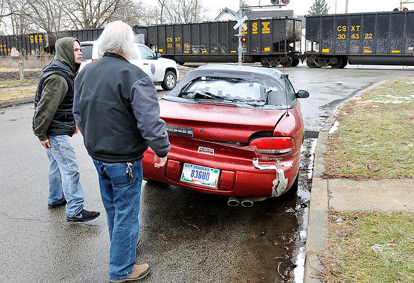 John P. Cleary   The Herald Bulletin<br /> The passenger in this car, left, talks to a area resident after escaping injury as the vehicle was struck by a CSX train Monday afternoon in the 1600 block of Walnut Street. According to police on the scene the car was heading south on Walnut when the brakes failed approaching the crossing, the driver then accelerated to beat the oncoming train but was clipped in the left rear corner and spun around 180 degrees and ended up facing north next to the curb as if it was parked there. The driver also was uninjured in the incident.