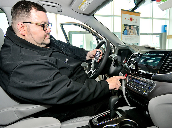 John P. Cleary   The Herald Bulletin<br /> Tom Wood Honda salesman Corey Pritt shows the push button start feature of this Honda with the vehicle fob. The fob has to be within three feet of the car for the starting system to work.