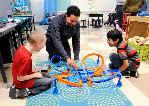 Don Knight   The Herald Bulletin<br /> NTN plant manager Tyrone Thomas races toy cars with Blade Kilk, left, and Christian Lopez during the opening of the new awards room at Anderson Elementary on Wednesday.