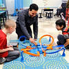 Don Knight | The Herald Bulletin<br /> NTN plant manager Tyrone Thomas races toy cars with Blade Kilk, left, and Christian Lopez during the opening of the new awards room at Anderson Elementary on Wednesday.
