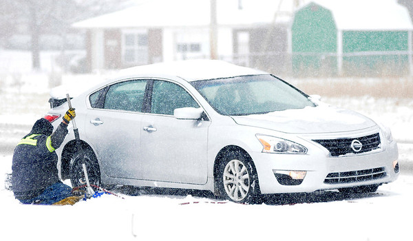 Don Knight | The Herald Bulletin<br /> Northwest towing helps a motorist with a flat tire on Indiana 32 during Saturday's snowstorm.