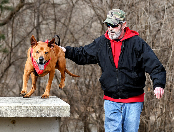 Rodney Ricker runs his dog Patriot through his workout as they go around the trails at Shadyside Lake Tuesday afternoon.. Patriot is a 4 year-old Rhodesian Ridgeback with lots of energy.