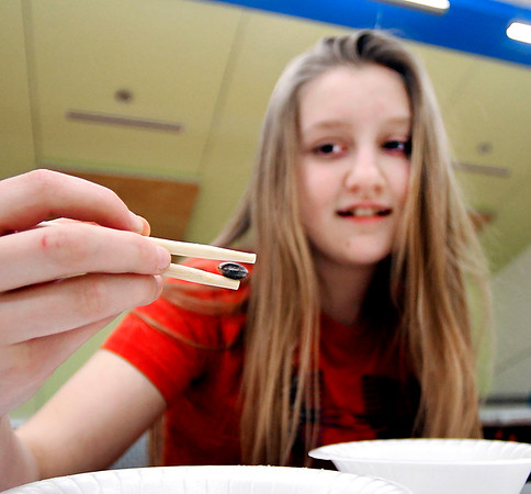 Gracie Bolton, 12, gets a firm grip on a m&m's piece of candy with her chopsticks as she participates in a chopstick challenge during the Teen Chinese New Year Celebration at the Anderson Public Library Wednesday evening. Participants had to transfer 50 m&m's from one bowl to another using only their chopsticks.