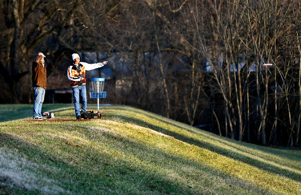 These two golfers take their shots from on top of the levee into the setting sun Tuesday afternoon as they play disc golf at Edgewater Park since the river has receded back into it's banks from the recent heavy rains drying out the course.
