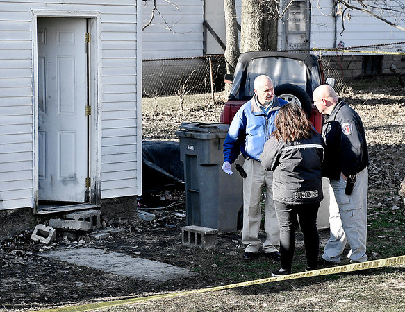 Anderson Police investigators confer with Madison County Coroner Danielle Noone outside the detached garage where two bodies were found Wednesday afternoon in the 300 block of East 31st Street.