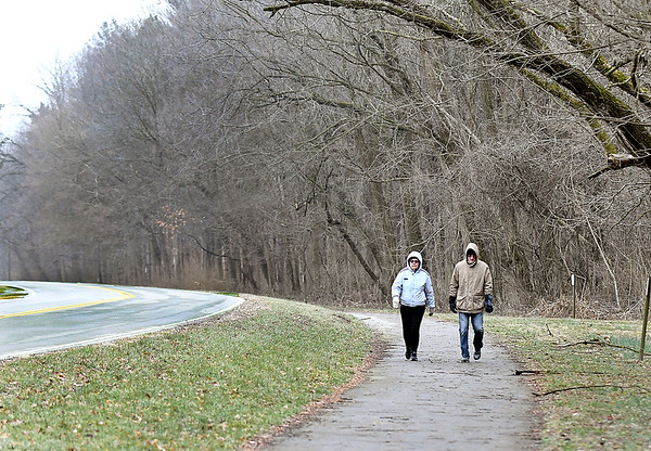 Bonnie and Tim Barnard walk the path along Mounds Road Monday afternoon that runs from the entrance of Mounds State Park to Chesterfield. Bonnie said they decided to walk this path because the trails in the park are still to muddy.