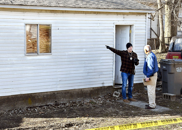 Anderson Police investigators confer as they work the scene of a detached garage where two bodies were found Wednesday afternoon in the 300 block of East 31st Street.