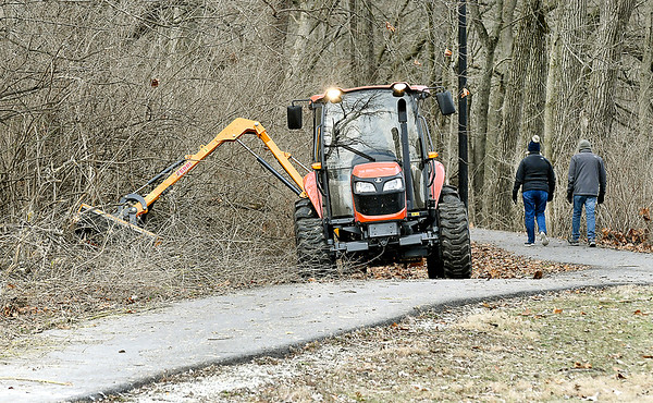 The Anderson Parks Department has been clearing away the underbrush from around the walking trails and banks of Shadyside Lake to open up the view of the lake and access points for fishing. Here they are using a power-takeoff cutter to knock down the brush as walkers stroll by.