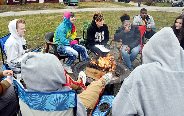 COMPASS Director Kristal McCorkle, center, sits around the fire with her students as they participate in a burning ceremony Monday.