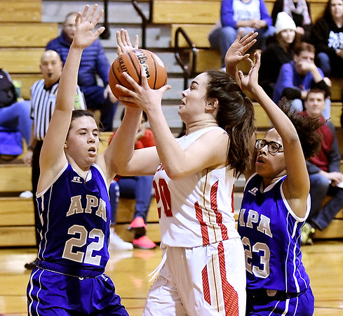 Liberty Christian's Elena Tufts drives the lane for a shot as APA's Chelsea Klepfer and Kaliyah Armstrong try to defend.