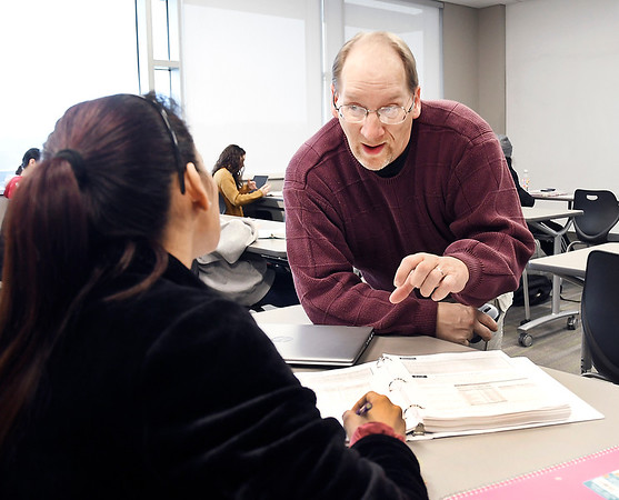 Ivy Tech assistant professor Duane Wolfe assists a student as she works through a problem in his Quantitative Reasoning class Monday.