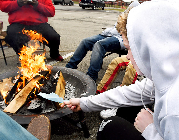 COMPASS student Andrew Coppess puts his letter into the fire as part of the burning ceremony.