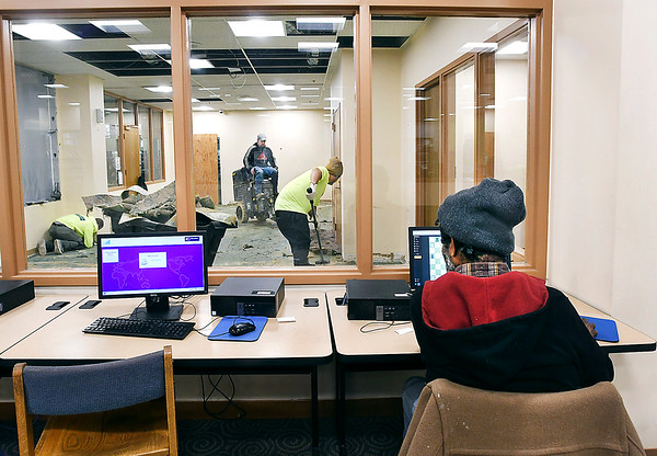 As a Anderson Public Library patron uses one of the computers, workers from Indiana Flooring were busy tearing out the old carpet from the teen room seen through the window Wednesday afternoon. The work is part of a $2.5 million renovation of the mail floor of the library.