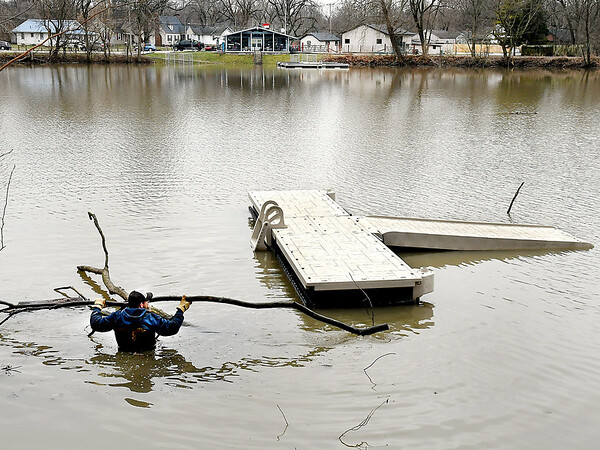 Kevin Grim, of LakeMaster Inc. of Muncie, wades into Shadyside Lake Monday afternoon to try and secure a section of docking that broke away from the bait house area due to the high water levels after heavy rains over the weekend. LakeMaster was the company that installed the new docks at the lake this past summer.