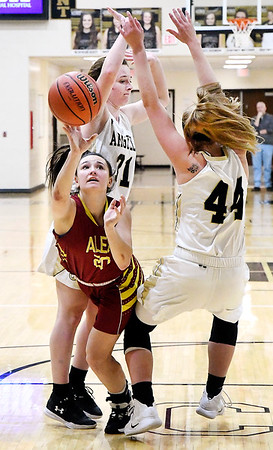 Alexandria's Reiley Hiser tries to take a shot as she falls down after squeezing between Madison-Grant's Zoey Barnett and Gracey Fox in the lane.